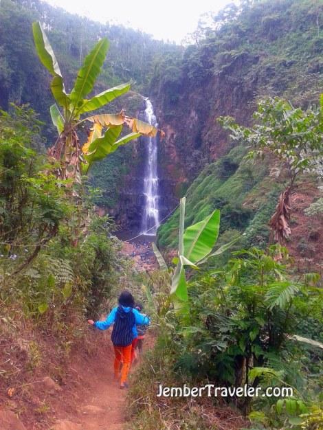Anak kecil berjalan menuju air terjun